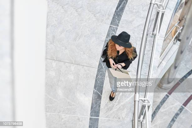 mid adult woman wearing a hat going shopping inside of a mall - shopping centre stock photos and pictures
