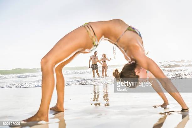 Mid adult woman wearing bikini bending over backwards on beach, Cape Town, South Africa
