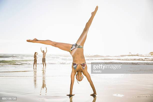 Mid adult woman wearing bikini cartwheeling on beach, Cape Town, South Africa