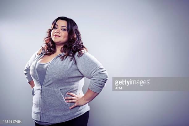 mid adult woman wearing grey top, hands on hips - hands in her pants fotografías e imágenes de stock