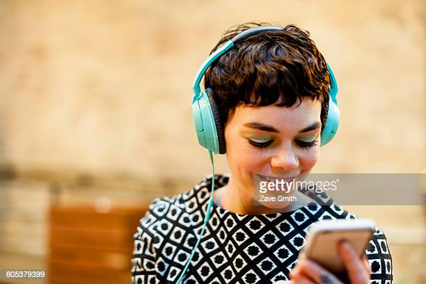 mid adult woman, wearing headphones, looking at smartphone, smiling - hitech mod a stock pictures, royalty-free photos & images