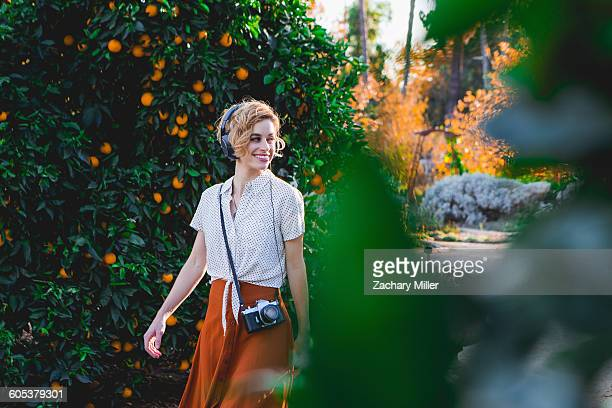 mid adult woman wearing headphones, outdoors, smiling - pasadena california stock photos and pictures