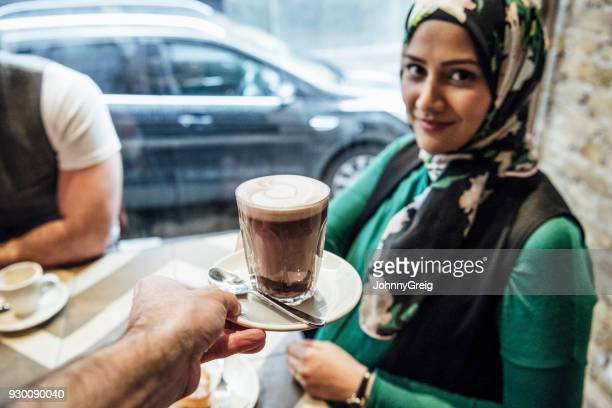 Mid adult woman wearing hijab being served coffee in cafe