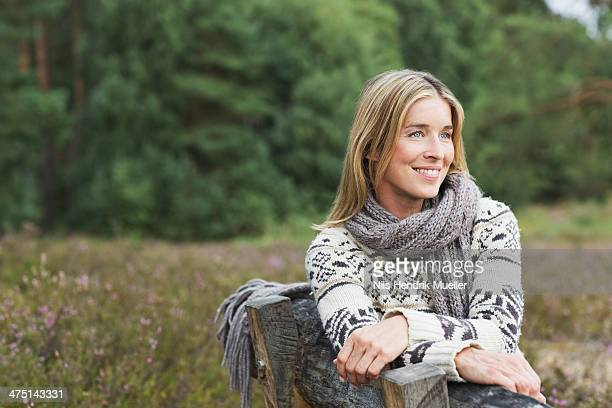 mid adult woman wearing sweater on bench - mid adult woman sweater stock pictures, royalty-free photos & images