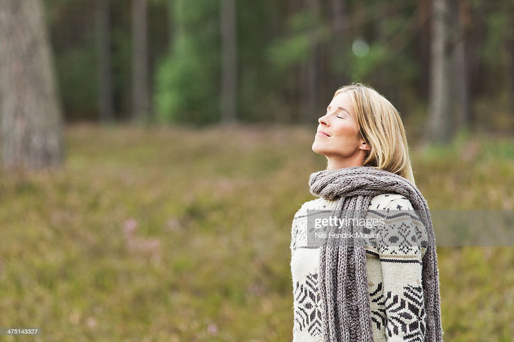 Mid adult woman wearing sweater with eyes closed : Stock Photo