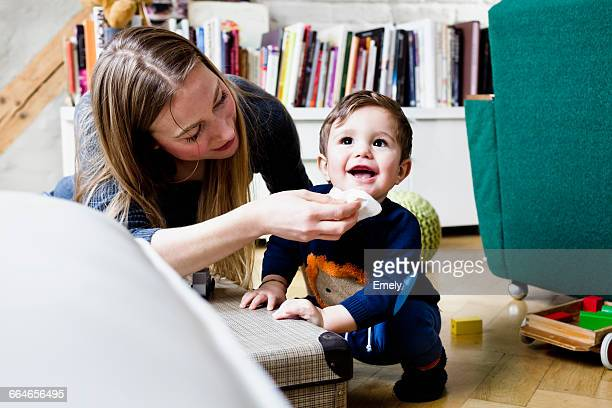 mid adult woman wiping baby sons chin with tissue in living room - rubbing stock photos and pictures