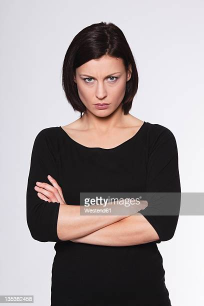mid adult woman with arms crossed and staring against white background - misnoegd stockfoto's en -beelden