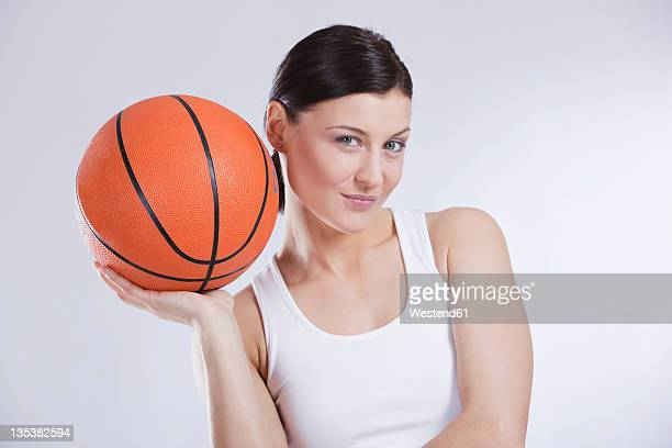 Mid adult woman with basket ball against white background, smiling, portrait