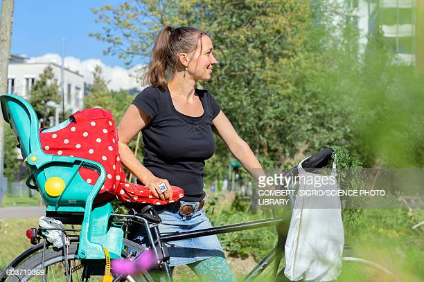 mid adult woman with bicycle in garden - sigrid gombert foto e immagini stock