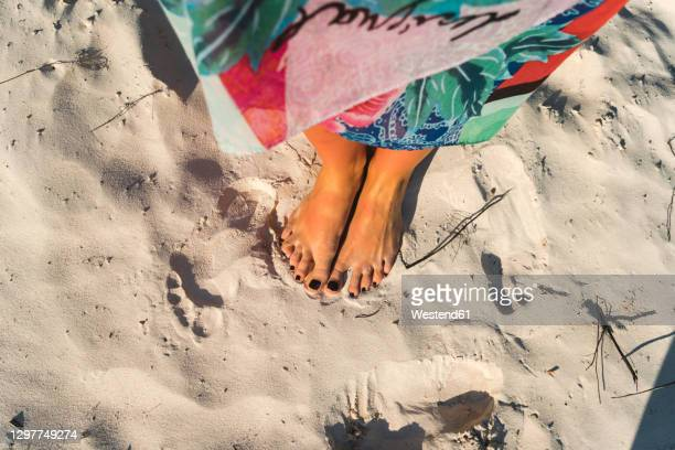 mid adult woman with black nail polish on feet at beach on sunny day - black nail polish stock pictures, royalty-free photos & images