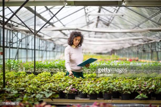 mid adult woman with clipboard working at garden center - scientificsubjects stock pictures, royalty-free photos & images