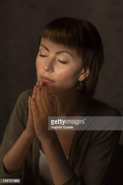 mid adult woman with closed eyes praying against gray background - mulher orando de joelhos imagens e fotografias de stock