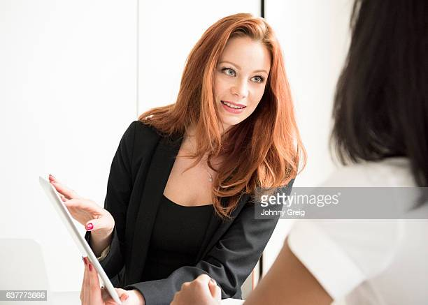 Mid adult woman with digital tablet talking to colleague