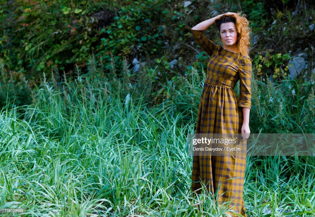 Mid Adult Woman With Hand In Hair Standing On Grassy Field : Photo