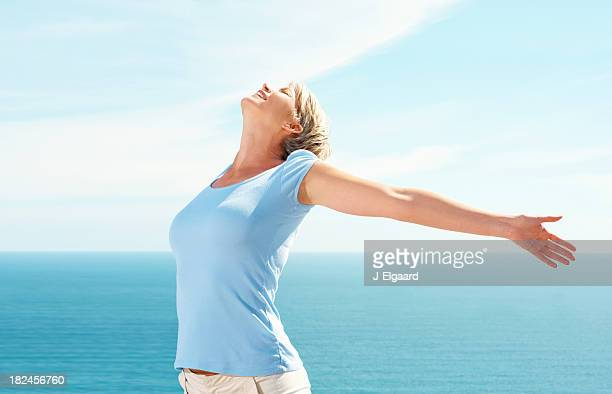 Mid adult woman with hands outstretched on a sunny day