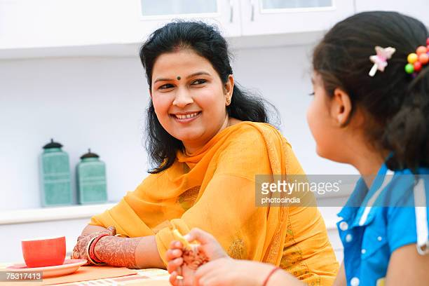 Mid adult woman with her daughter sitting at a dining table and smiling