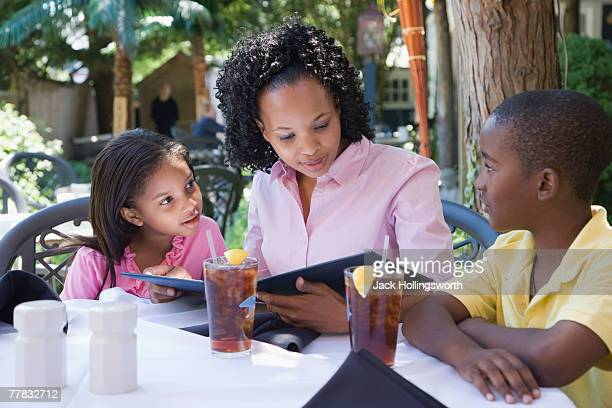 Mid adult woman with his son and daughter reading a menu at the breakfast table