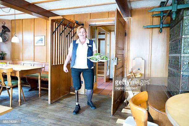 mid adult woman with prosthetic leg, holding plates of food - sigrid gombert imagens e fotografias de stock