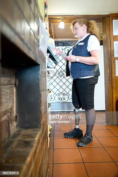 mid adult woman with prosthetic leg, working cash register at restaurant - sigrid gombert stock pictures, royalty-free photos & images