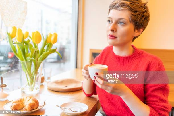 mid adult woman with short blond hair looking through cafe window - short hair stock pictures, royalty-free photos & images