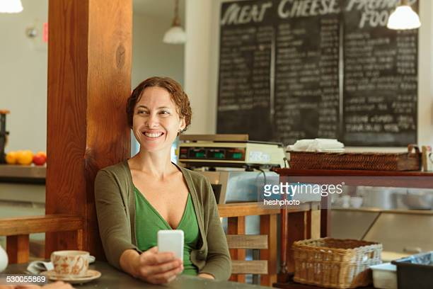 mid adult woman with smartphone in country store cafe - heshphoto stock pictures, royalty-free photos & images
