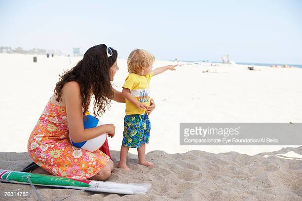 Mid adult woman with son (2-3) on beach