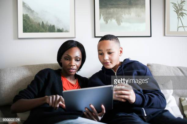 mid adult woman with son using digital tablet on sofa at home - home icon stock photos and pictures