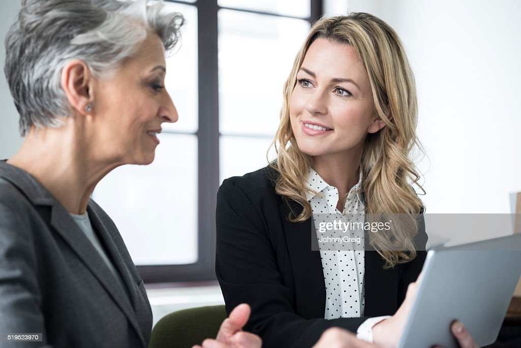 Mid adult woman with tablet smiling at mature colleague : Stock Photo