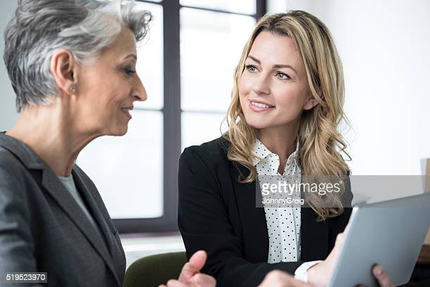 mid adult woman with tablet smiling at mature colleague - mid adult women stock pictures, royalty-free photos & images