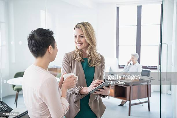 Mid adult woman with tablet talking to female colleague, smiling