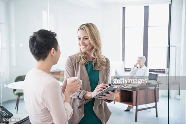30 代の女性がタブレットをする女性の同僚、笑顔