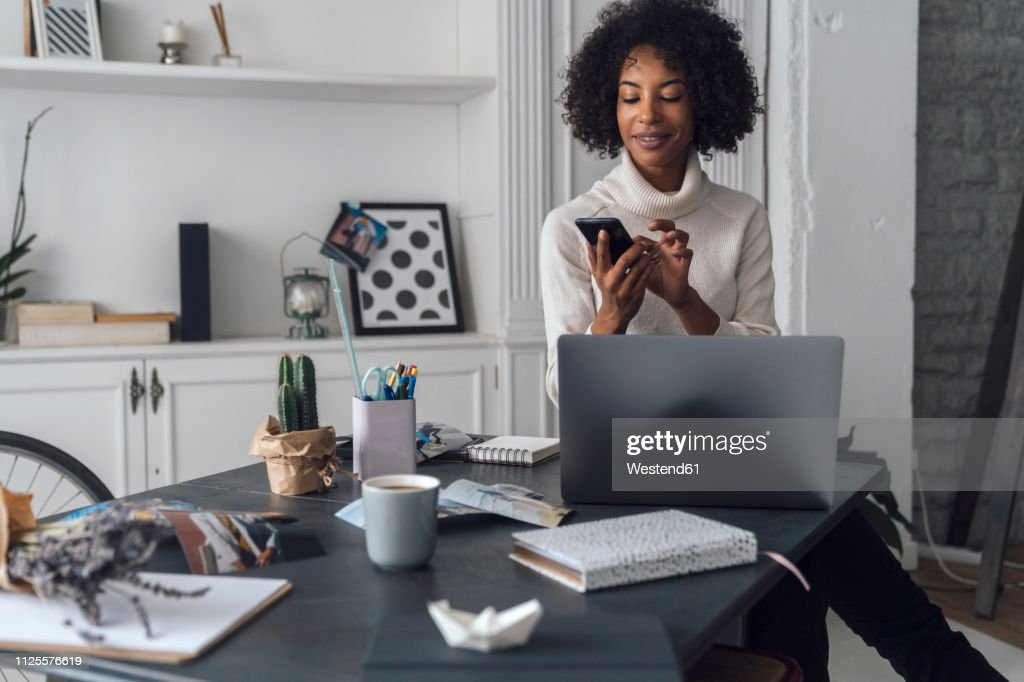 Mid adult woman working in her home office, using smartphone : Stock Photo