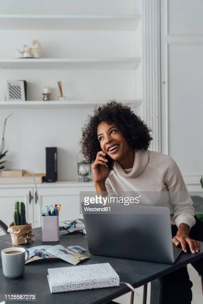 mid adult woman working in her home office, using smartphone - vertical stock pictures, royalty-free photos & images