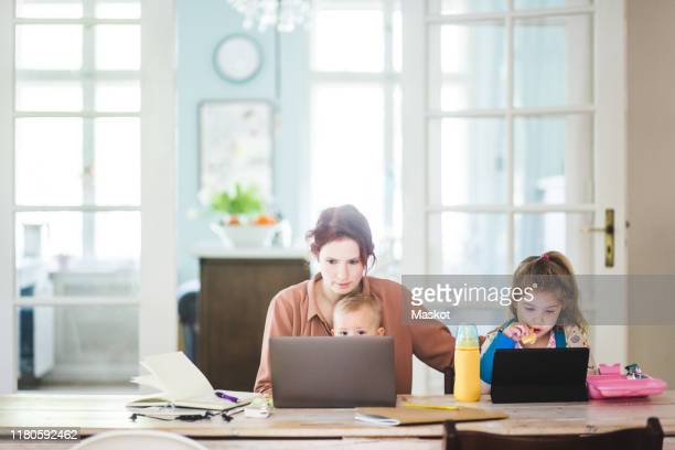 mid adult woman working on laptop while sitting with children at home - working mother stock pictures, royalty-free photos & images