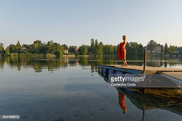 mid adult woman wrapped in towel, standing on jetty - varese stock pictures, royalty-free photos & images