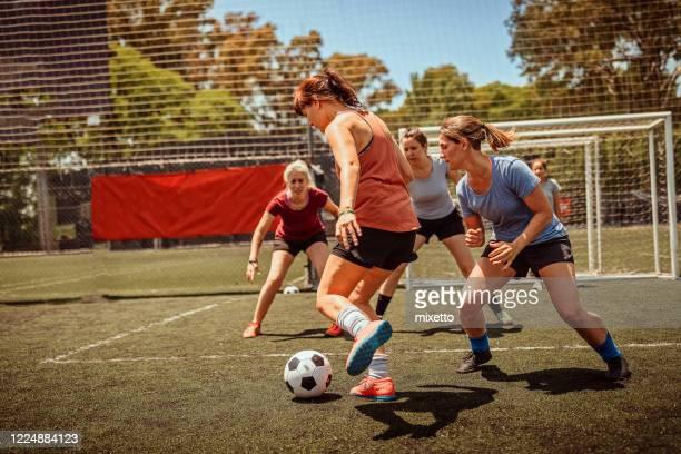 femmes adultes moyennes jouant au football sur le terrain - tacler photos et images de collection