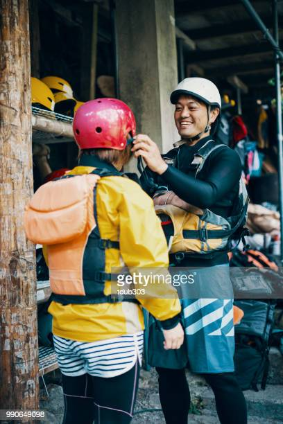 A mid adult women trying on a helmet in preparation for white water river rafting