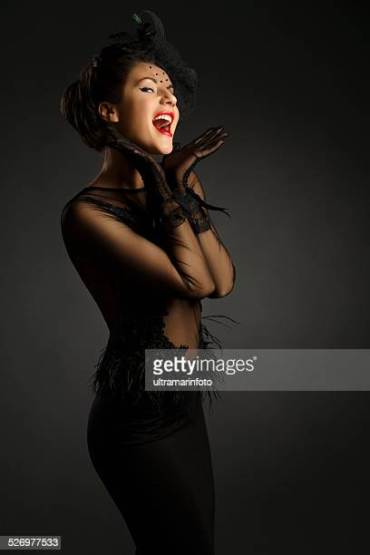 Donne di mezza età indossando abito nero glamorous retrò diva Cantare