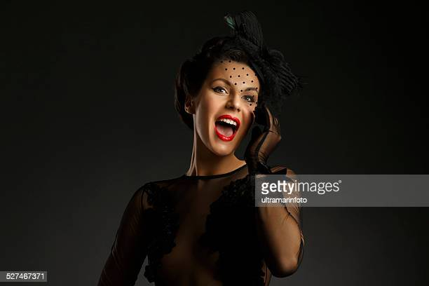 Mid adult women wearing black gown   Glamourous retro diva singing