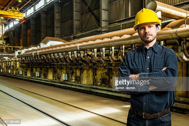 Mid Adult worker in yellow helmet inside factory interior