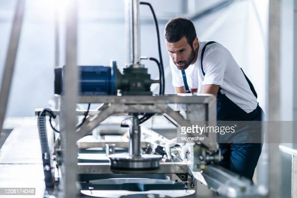 mittlere erwachsene arbeiter arbeiten an einer produktionslinie in einer fabrik. - maschinenbau stock-fotos und bilder