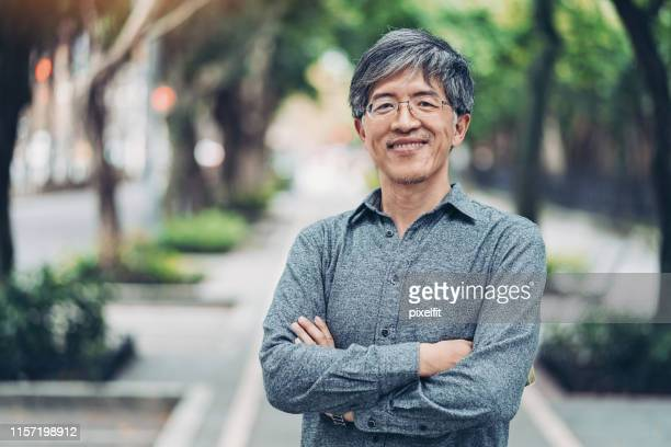 mid age chinese ethnicity man in the park - east asian culture stock pictures, royalty-free photos & images