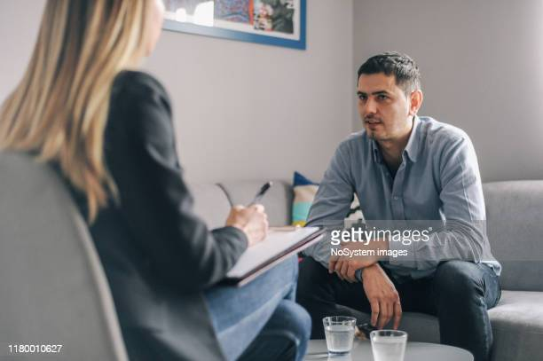 mid age man having on on one counselling meeting - mental health stock pictures, royalty-free photos & images