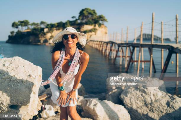 mid age woman portrait in front of cameo island in zakynthos, greece - greek islands stock pictures, royalty-free photos & images