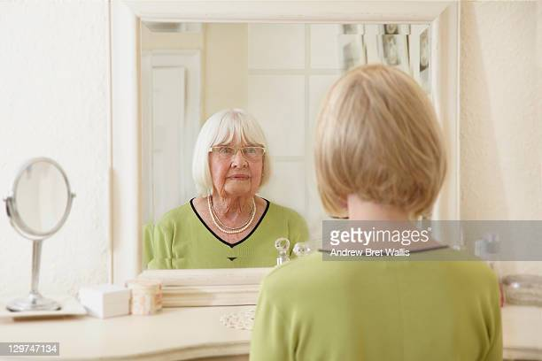 Mid age woman sees her senior self in the mirror