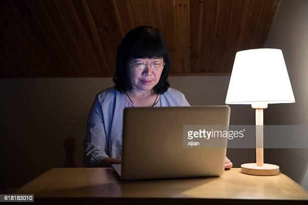 Mitte Alter Frau arbeitet zu Hause auf laptop