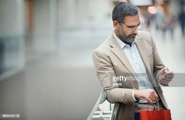Mi homme d'affaires âgé à un centre commercial