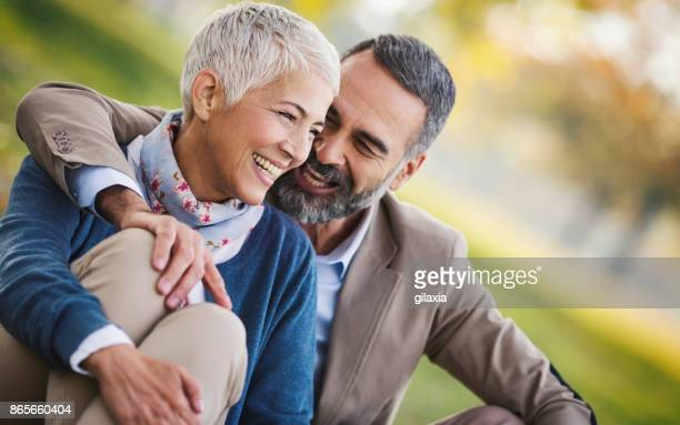 mid aged couple in a park - mid adult men stock pictures, royalty-free photos & images