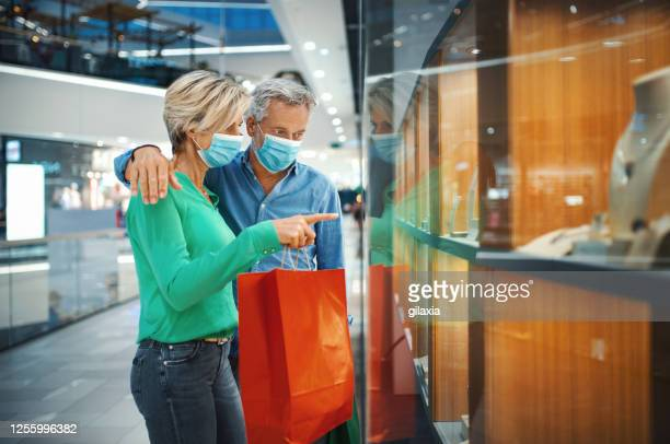 mid aged couple in a shopping mall during coronavirus. - jewellery stock pictures, royalty-free photos & images