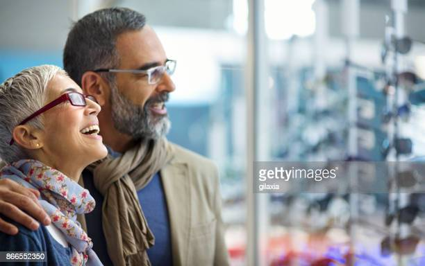 mid aged couple in a shopping mall. - eyewear stock pictures, royalty-free photos & images